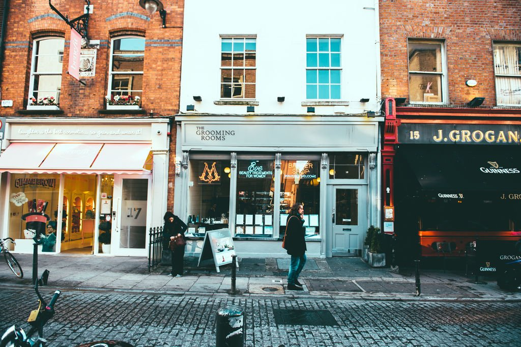 Pedestrians beside small storefronts in Dublin