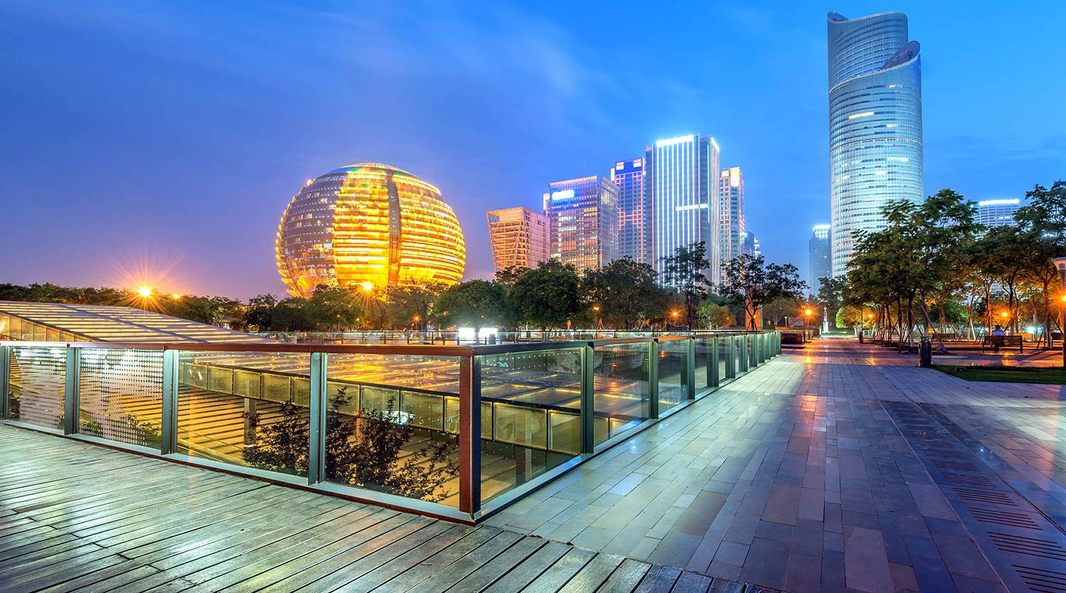 Urban buildings illuminated at dusk near a walkway in Hangzhou