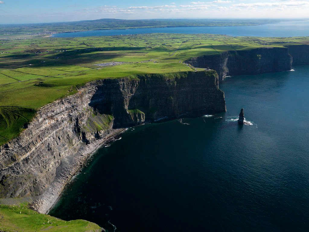 Steep jagged cliffs next to dark blue water comprise the coastline of Ireland