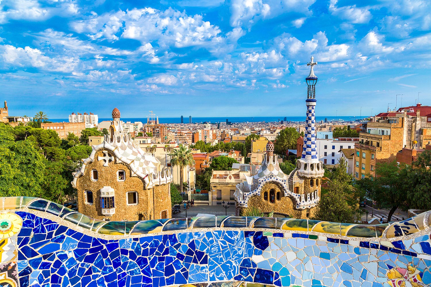 A blue-tiled, mosaic bridge overlooks the city of Barcelona