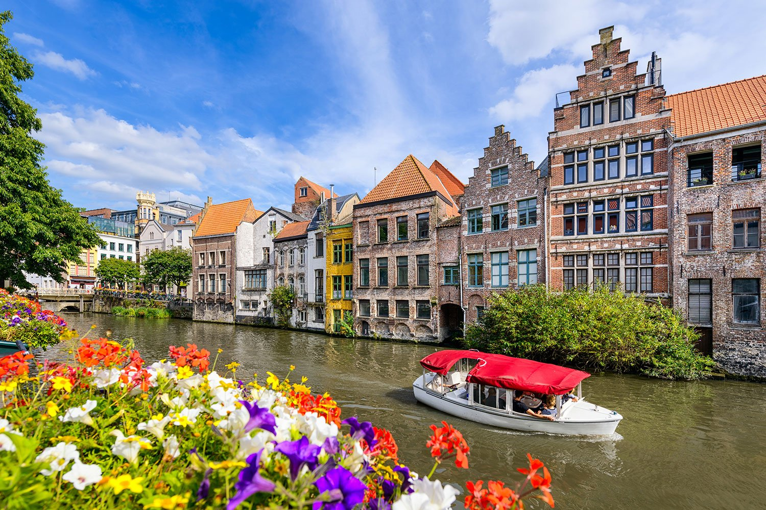 White and red boat on a canal lined by multi-level buildings and colorful flowers in Belgium