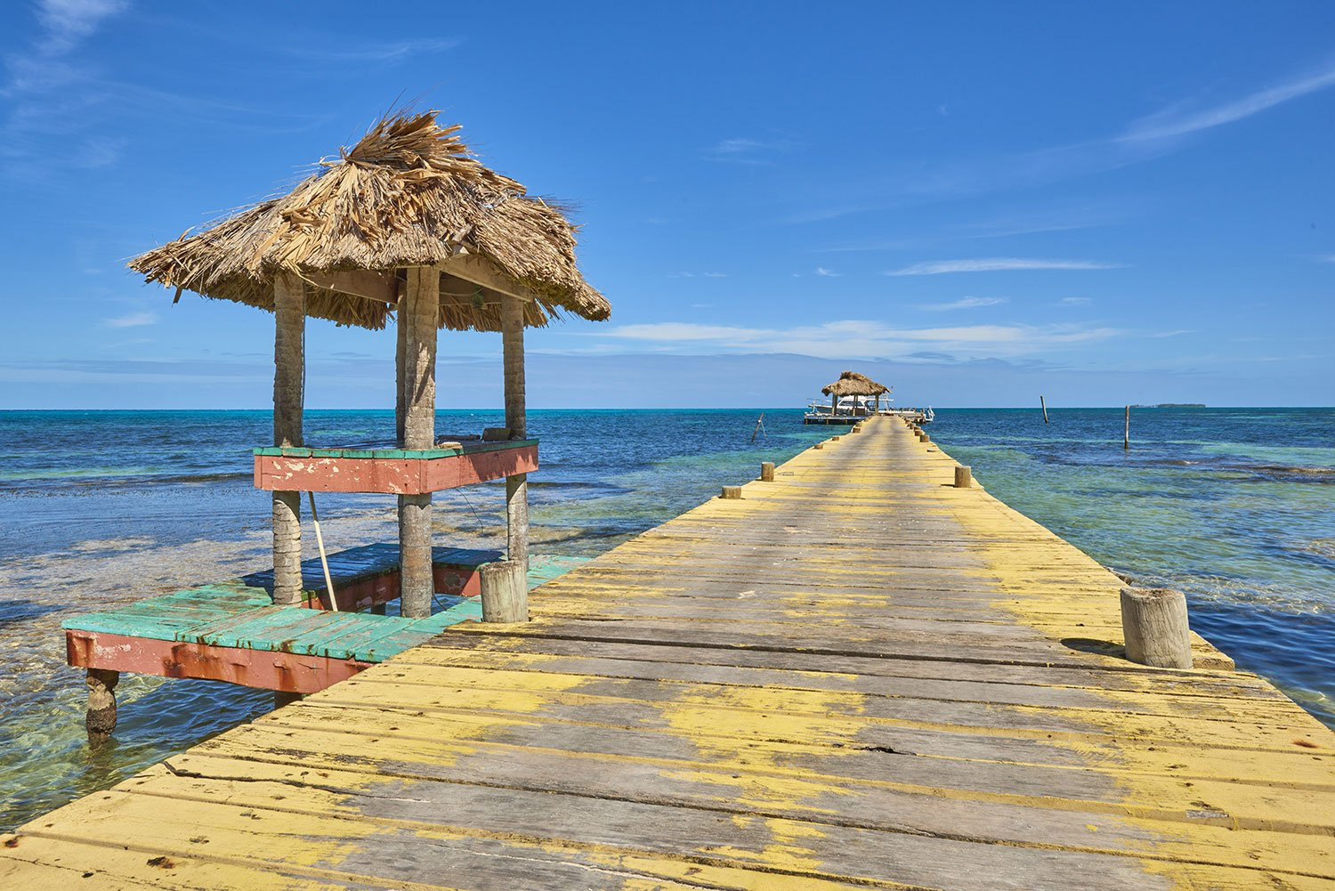 Wooden pier with yellow paint leading into the sea in Belize