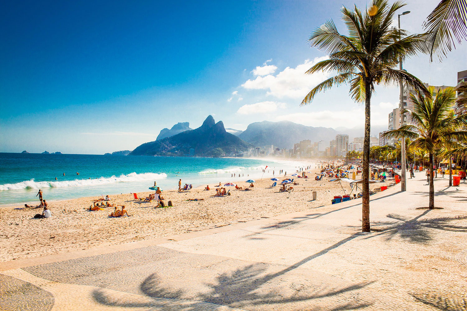 People on a sandy beach alongside palm trees and turquoise water in Brazil