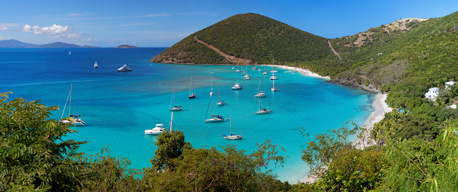Lush shoreline with gradient blue water and sailboats in the British Virgin Islands