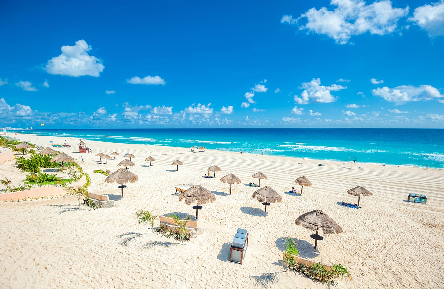 Beach umbrellas and chairs line the sand in Cancun