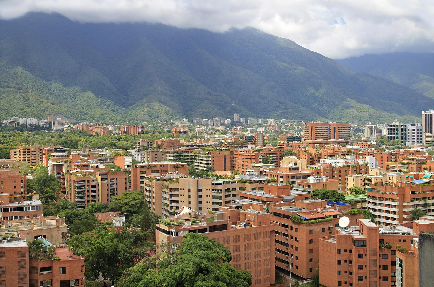 Aerial view of multi-level buildings in Caracas with mountains in the background