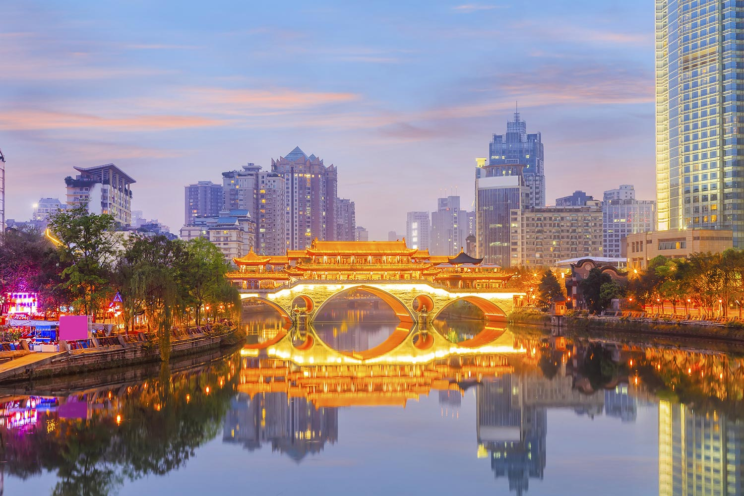 Illuminated bridge surrounded by urban buildings in Chengdu