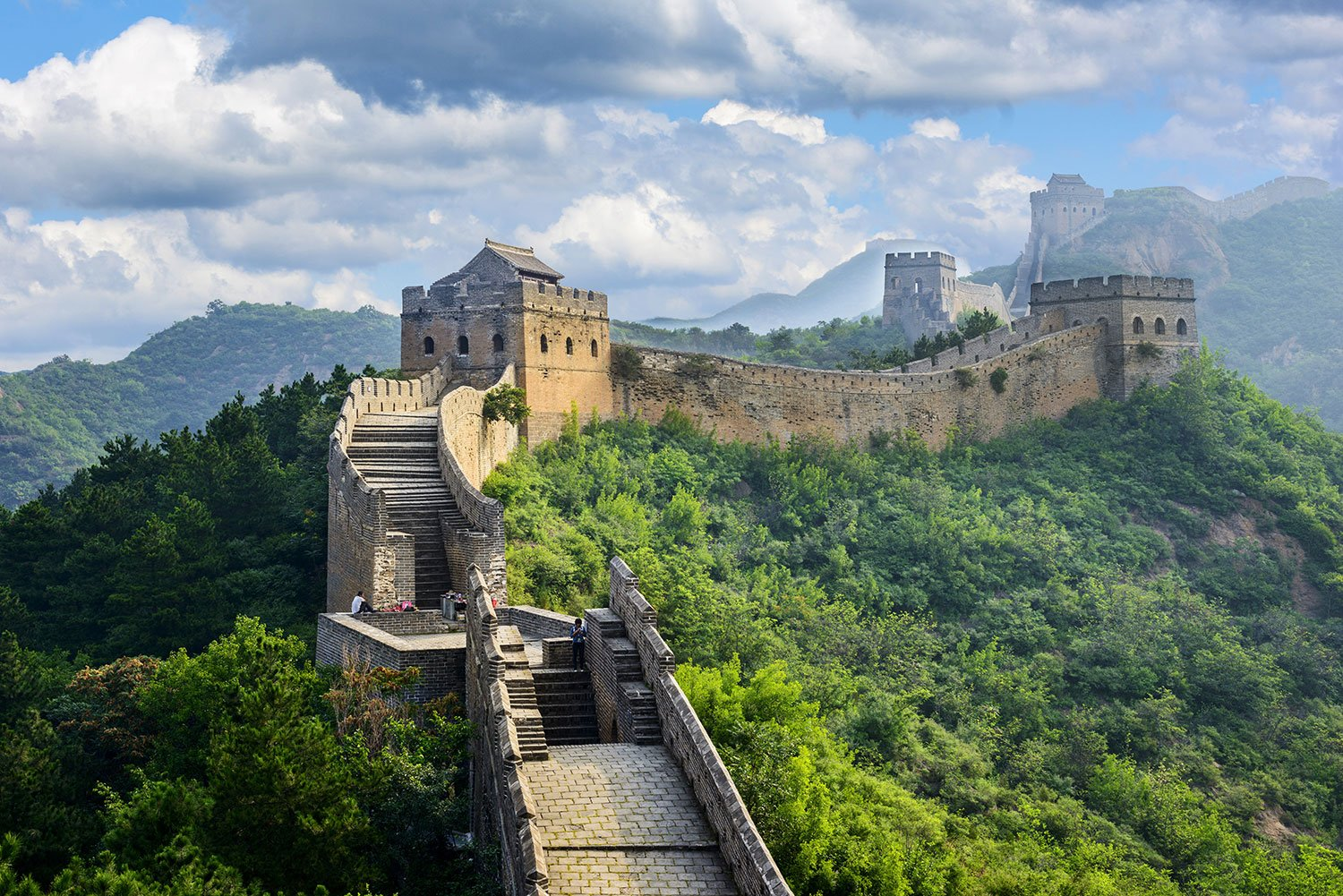 Great Wall of China on top of mountains with dense foliage