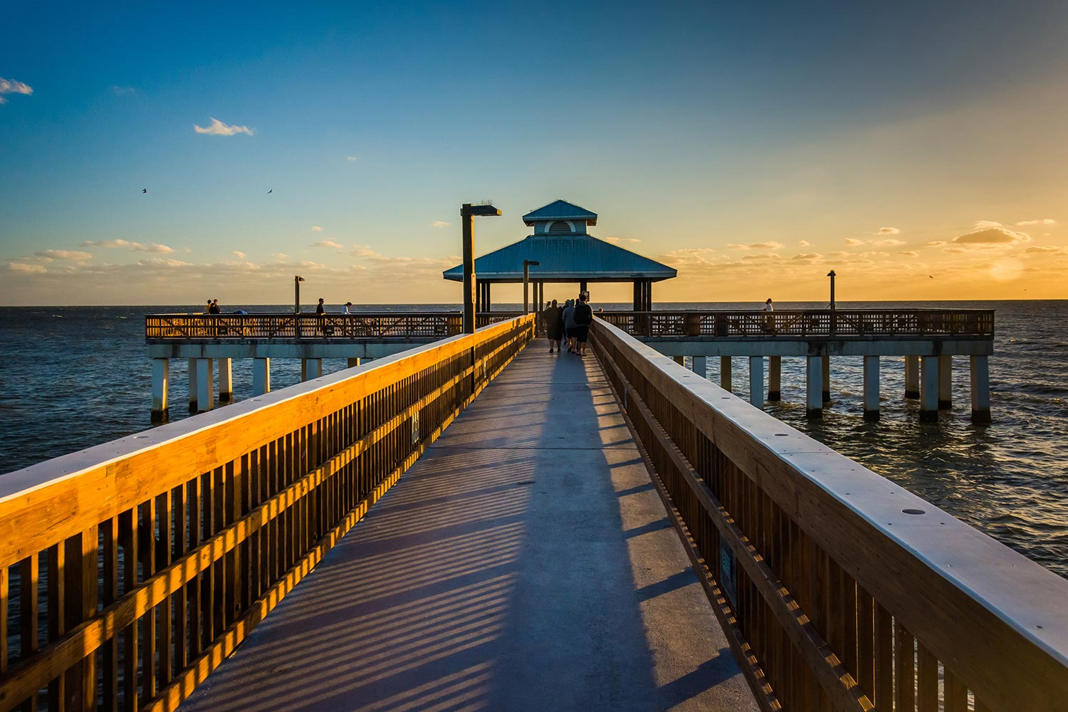 Sunset on a wooden pier with railings leading into the water in Fort Myers