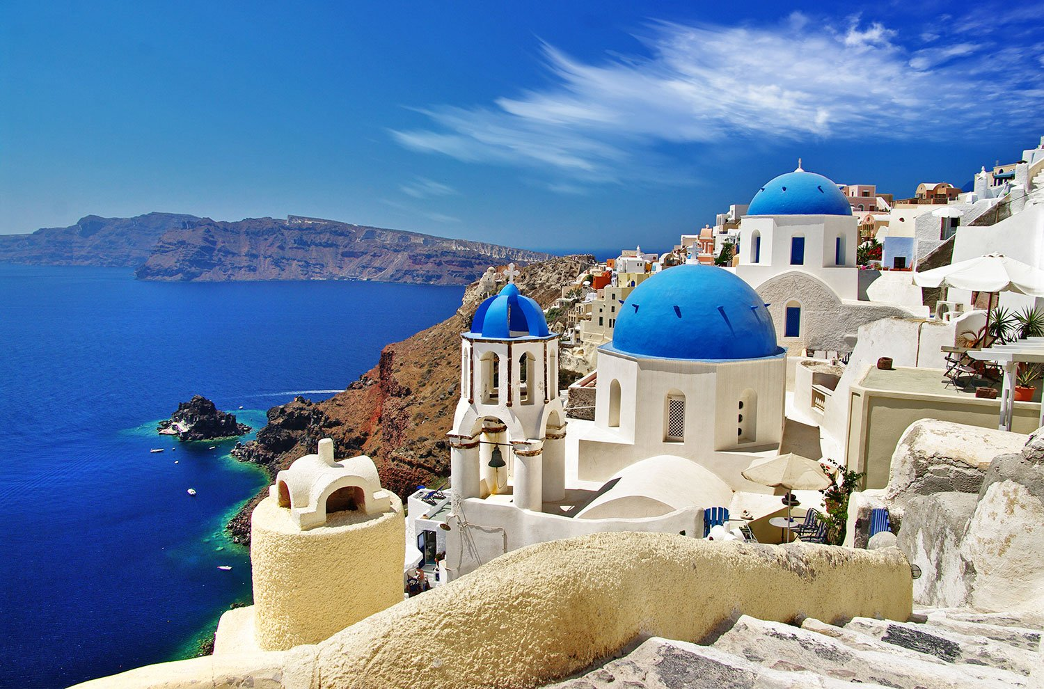 White buildings with blue domes next to the vibrant blue sea in Greece