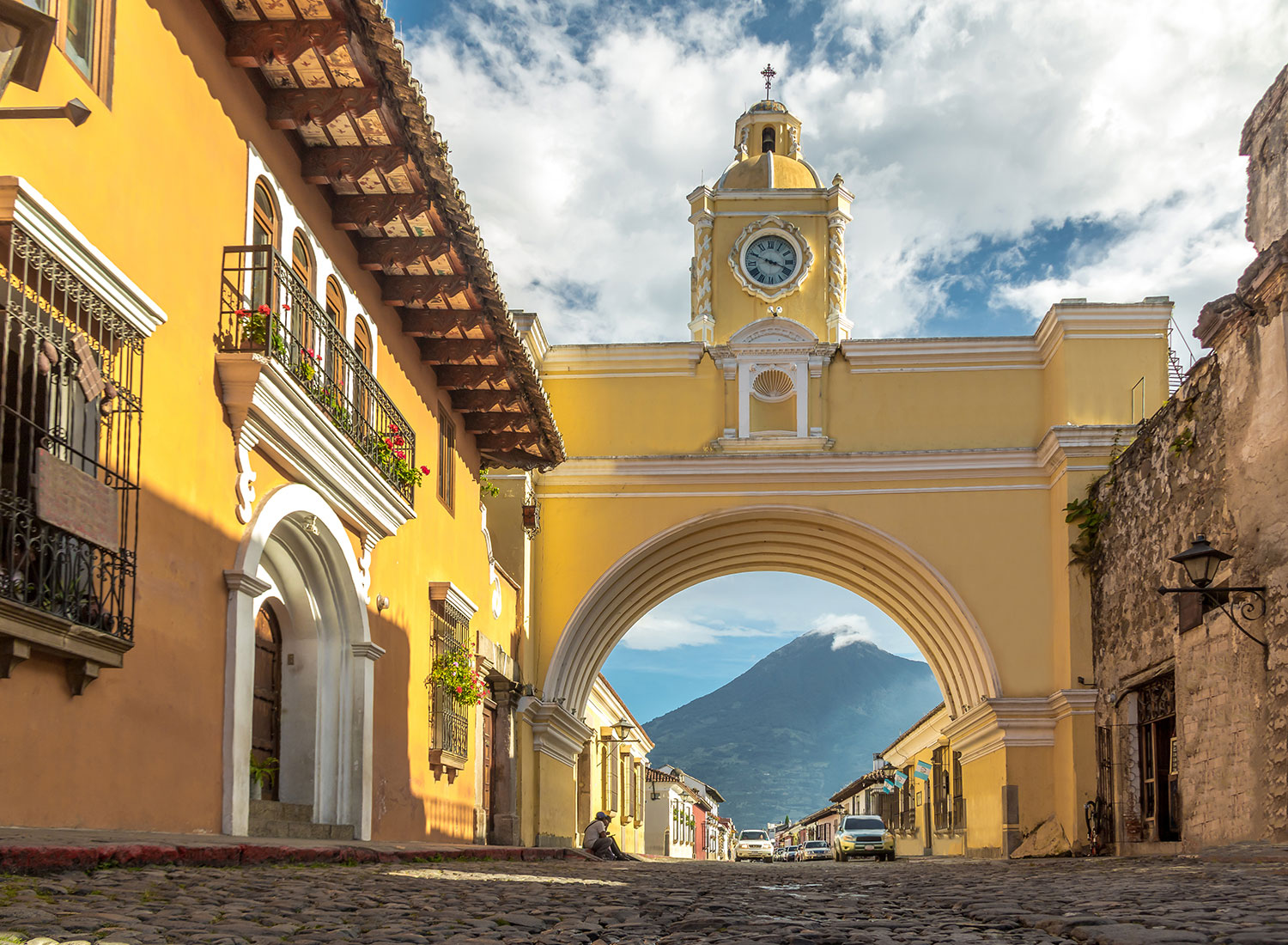 Yellow arched wall with a clock at the top of the structure in Guatemala