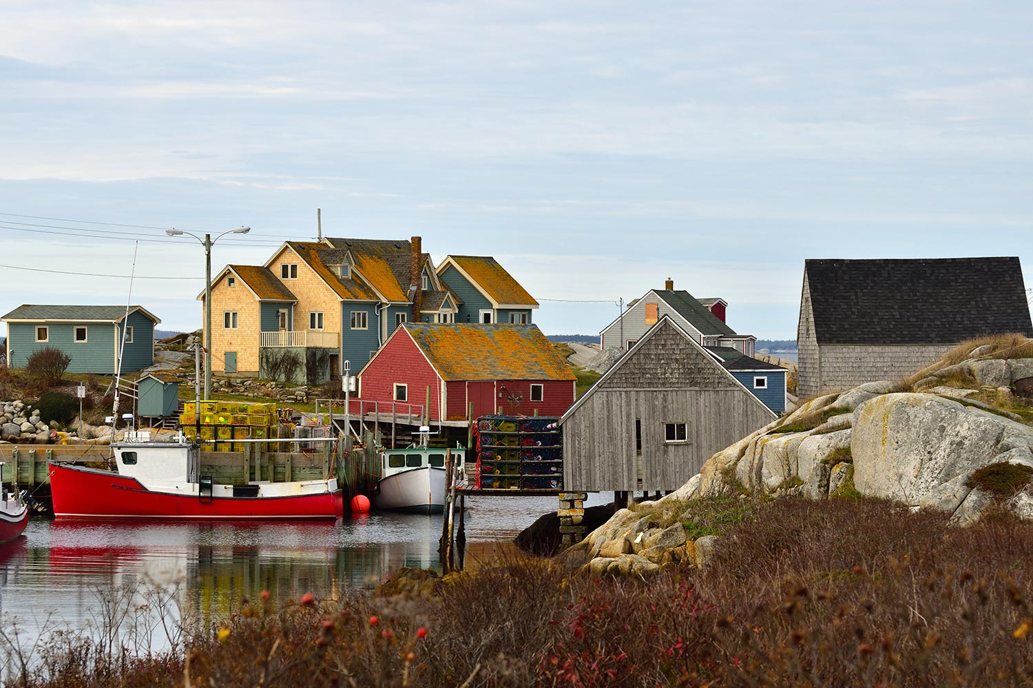 Colorful homes next to a red and white boat anchored in a body of glassy water in Halifax