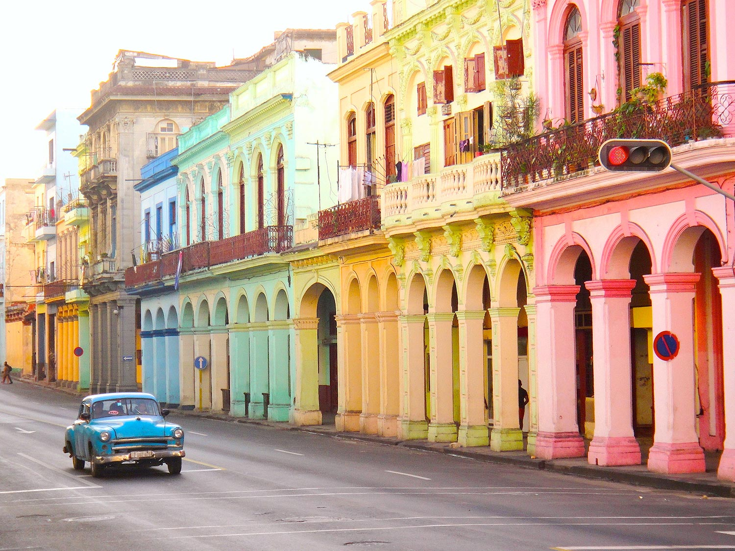 A row of buildings each a different color of the rainbow line a street in Havana