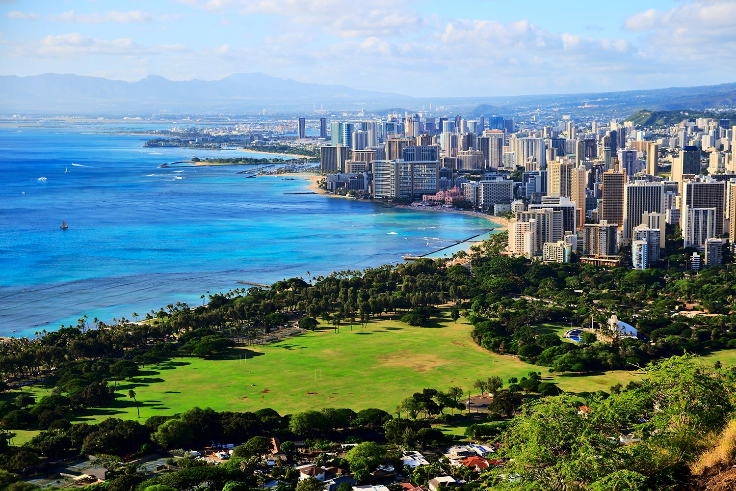 Curving coastline of Honolulu lining an urban landscape and green field