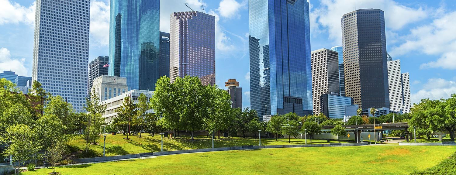 Houston skyscrapers border a grassy park