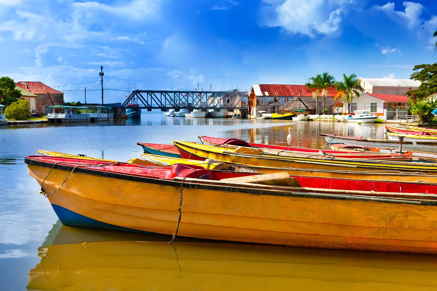 Small, brightly-colored boats line shallow water in Jamaica