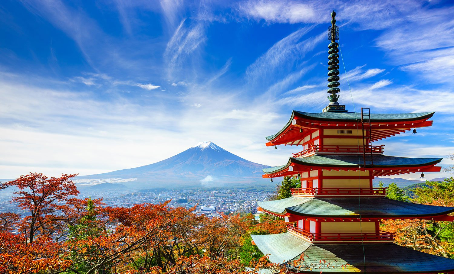 Traditional multi-tiered building with a mountain in the background on a sunny day in Japan