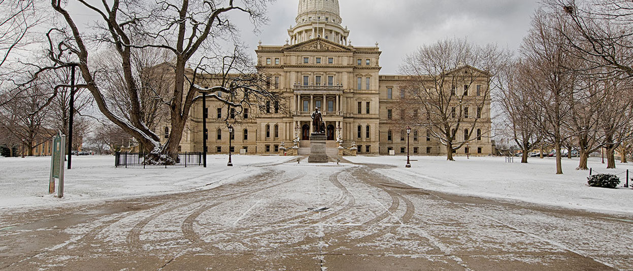 A snow-dusted path leads to the capitol building in Lansing