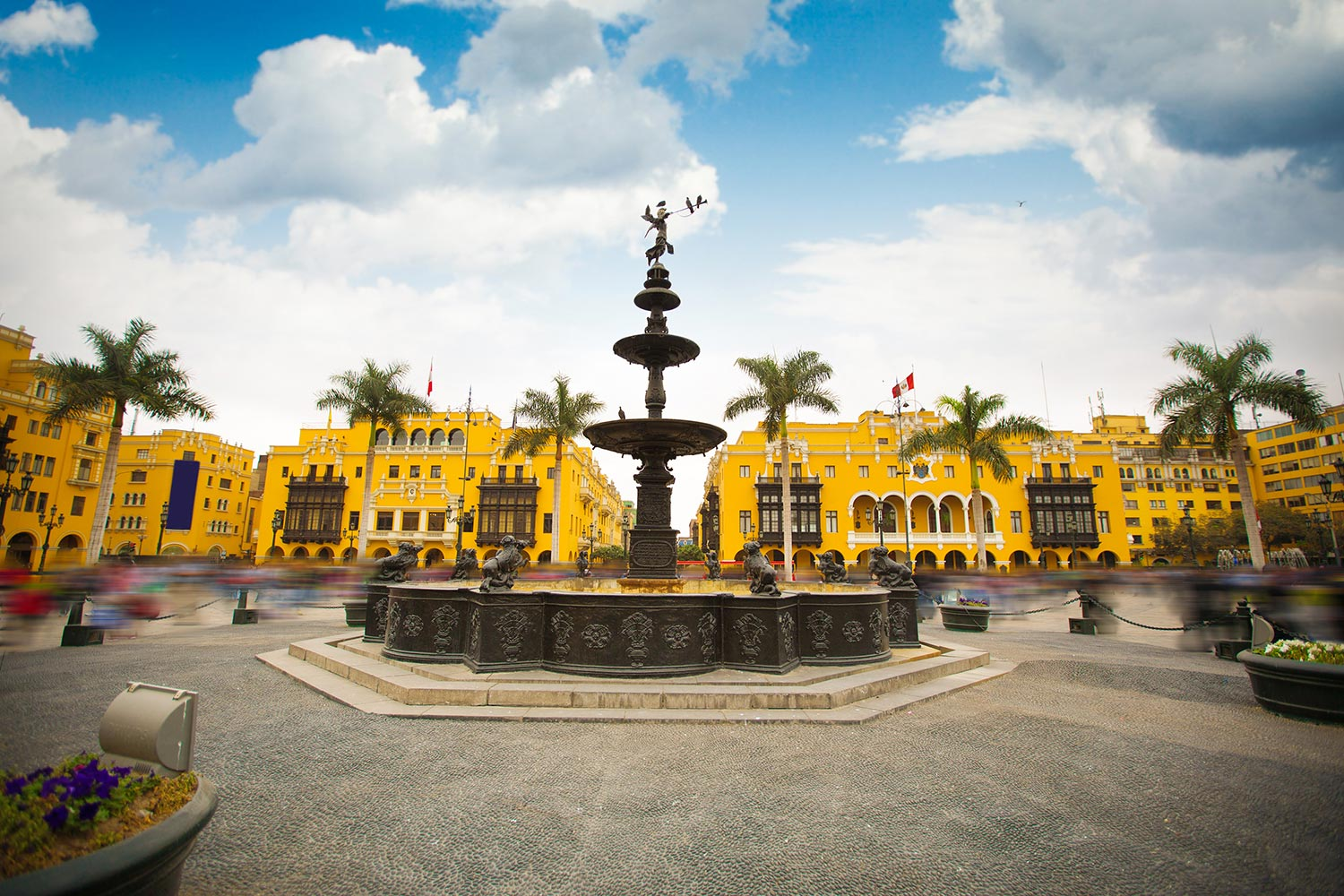 A row of yellow buildings stands in the background of a large fountain in the center of Lima