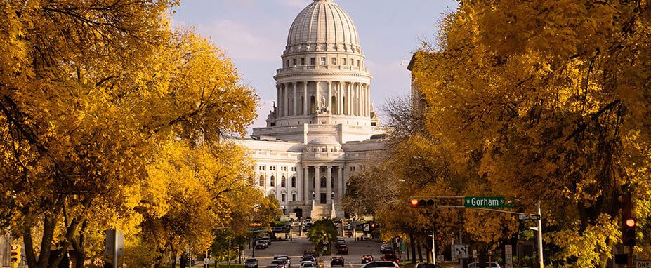 Trees in yellow and orange shades line the street leading up to the State Capitol building in Madison