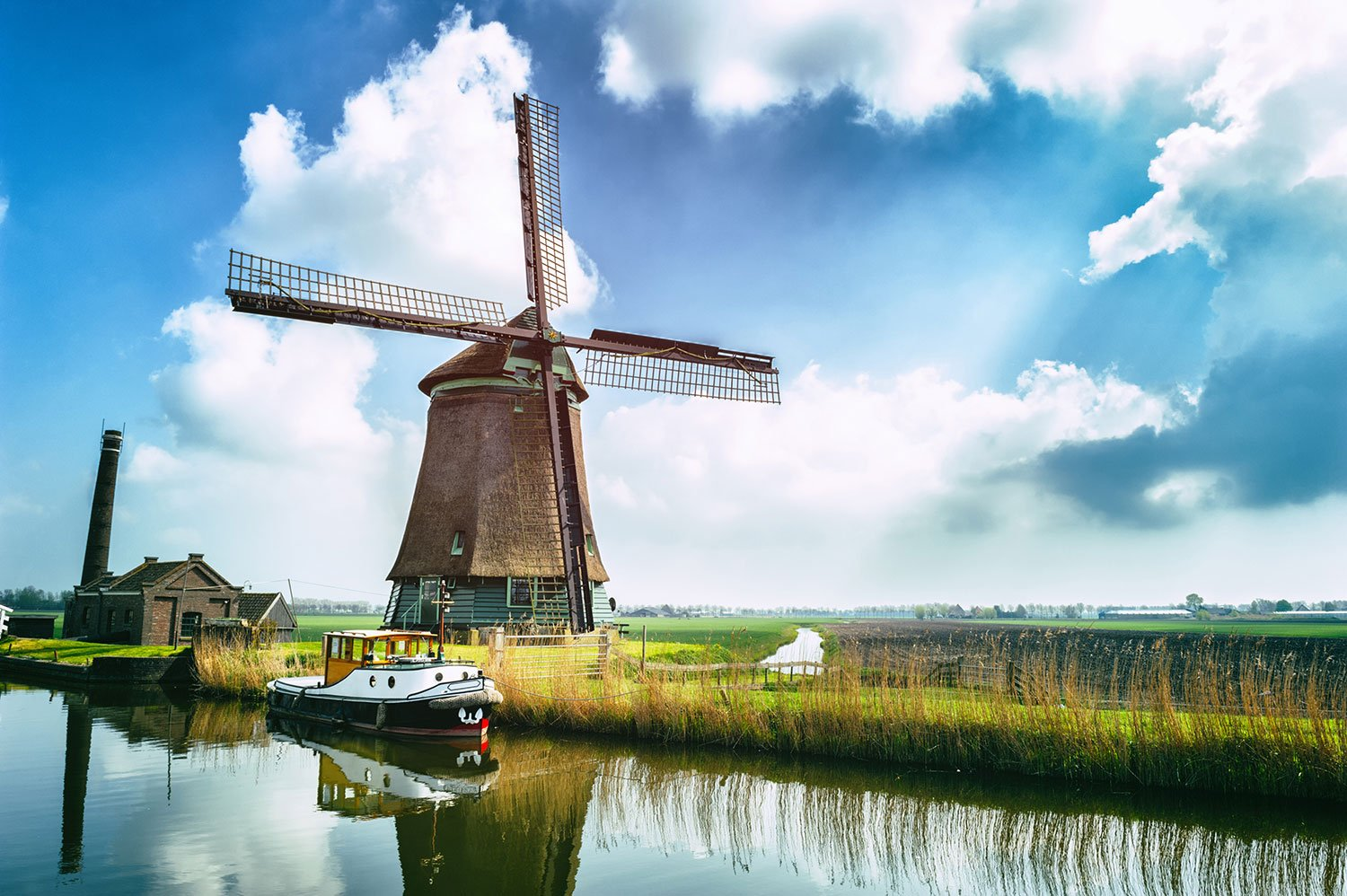 A wooden windmill next a small body of glassy water on a sunny day in the Netherlands