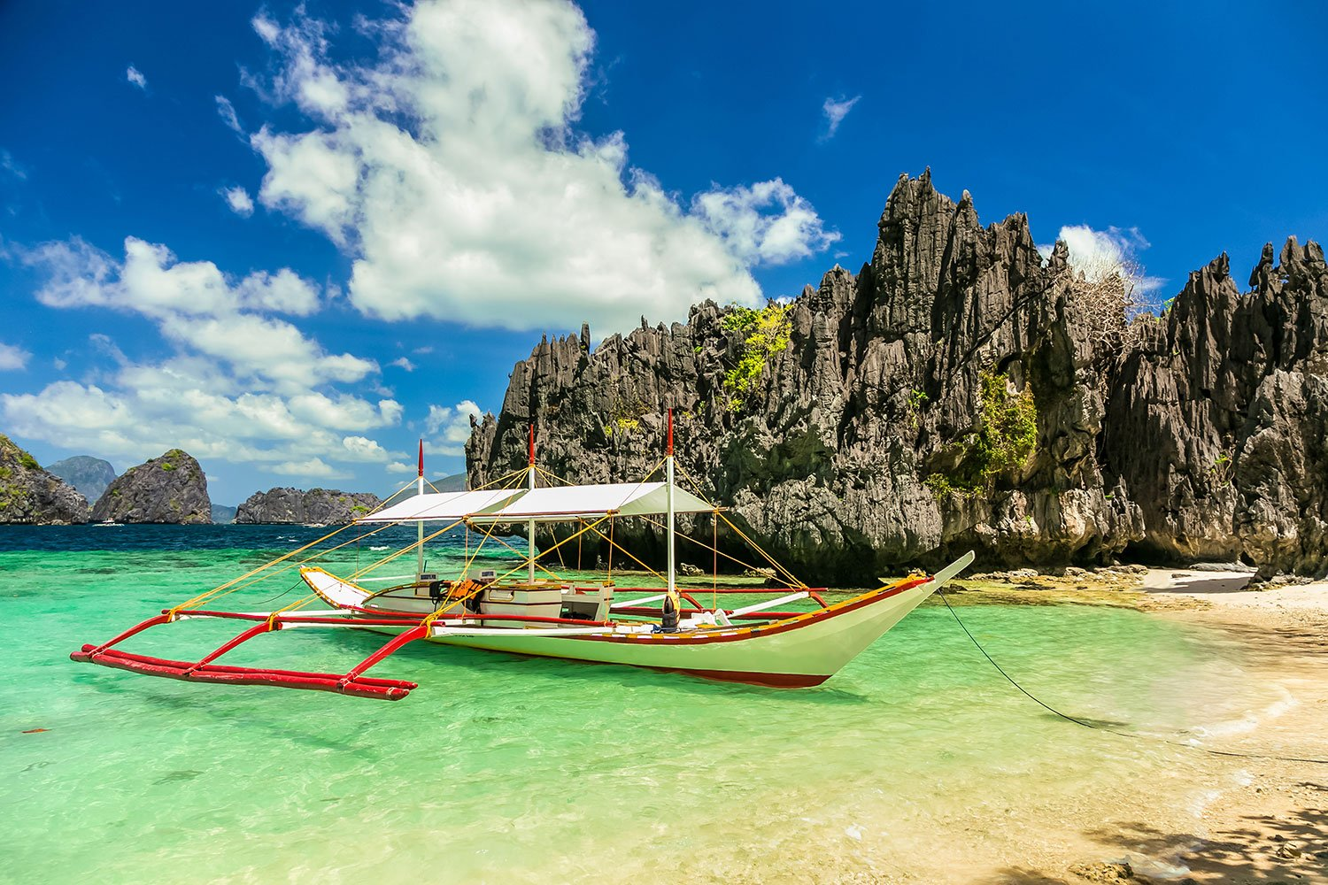 A red and white boat docks on the coast of the Philippines