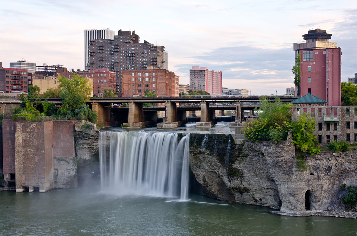 A waterfall runs under an elevated highway in Rochester, NY