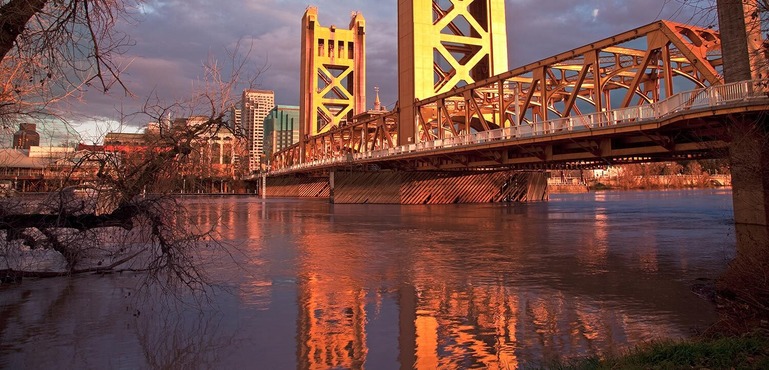 A large metal bridge above water in Sacramento