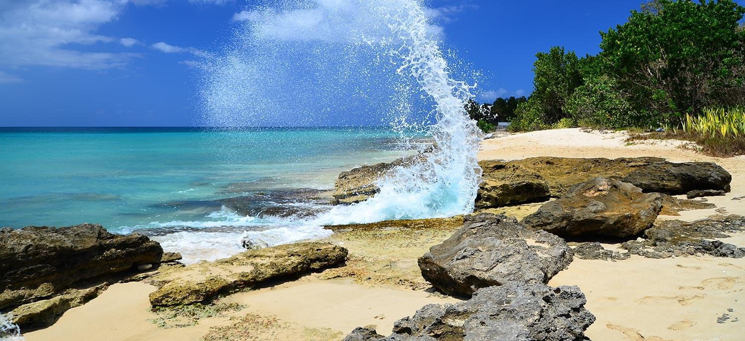 A wave splashes against rocks on a beach in Saint Croix