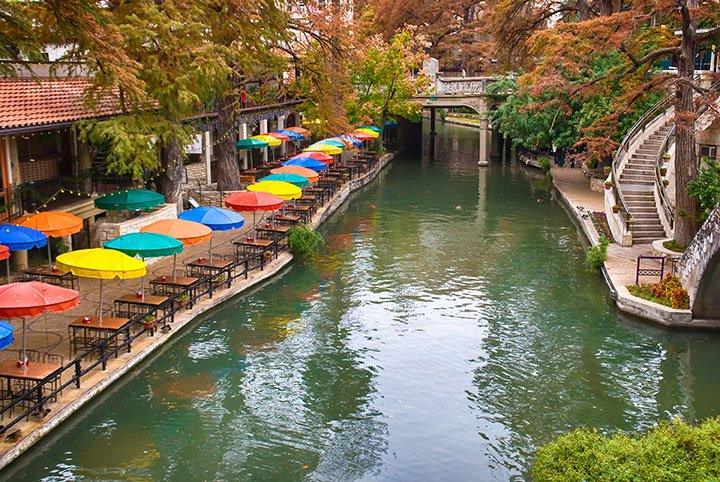 Colorful umbrellas line a walkway along blue-green water in San Antonio