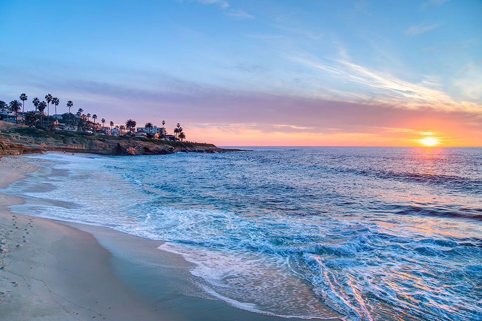 Water washes on to the sandy coast of San Diego at sunset