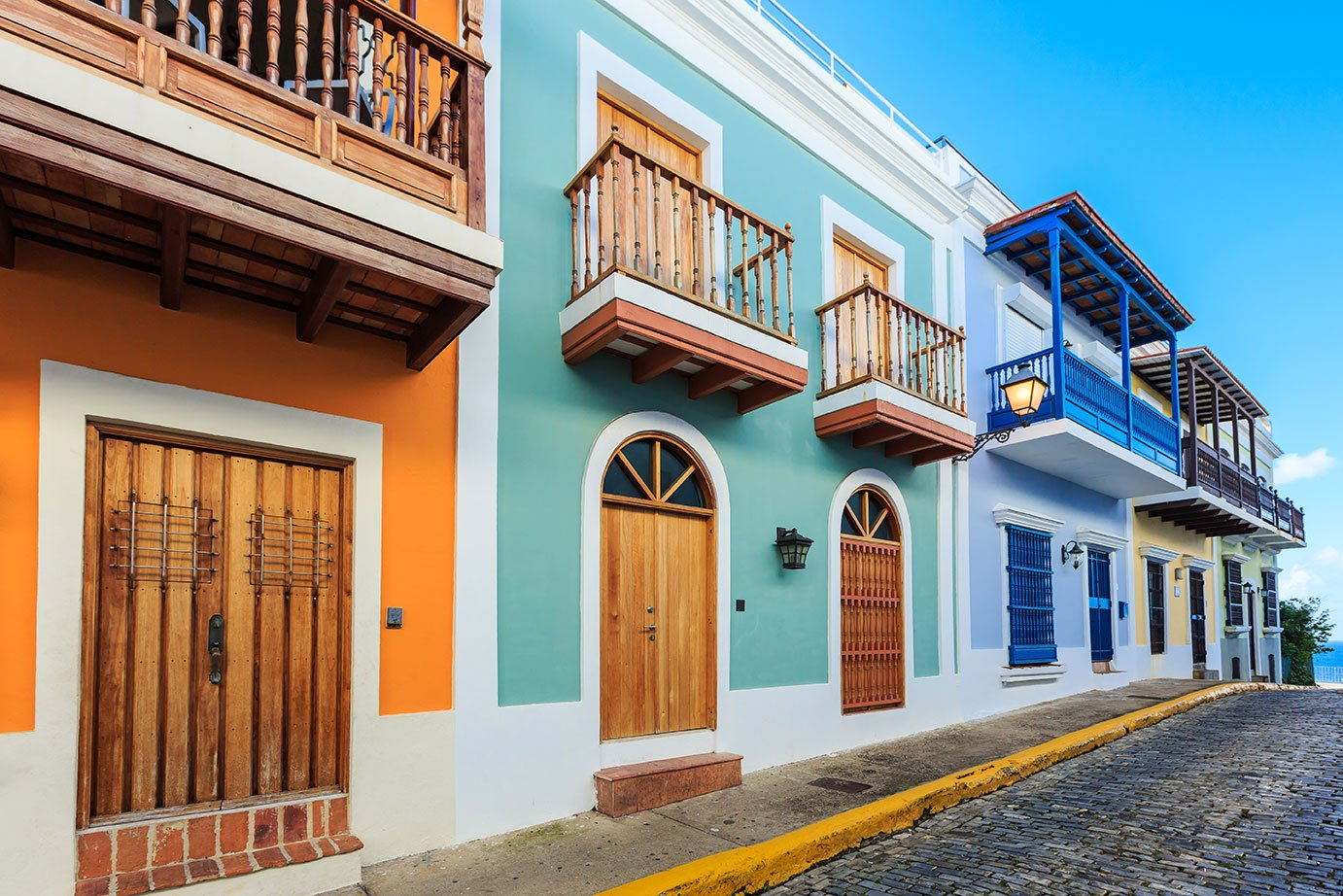 Two-story homes in orange, green, and blue line the streets of San Juan