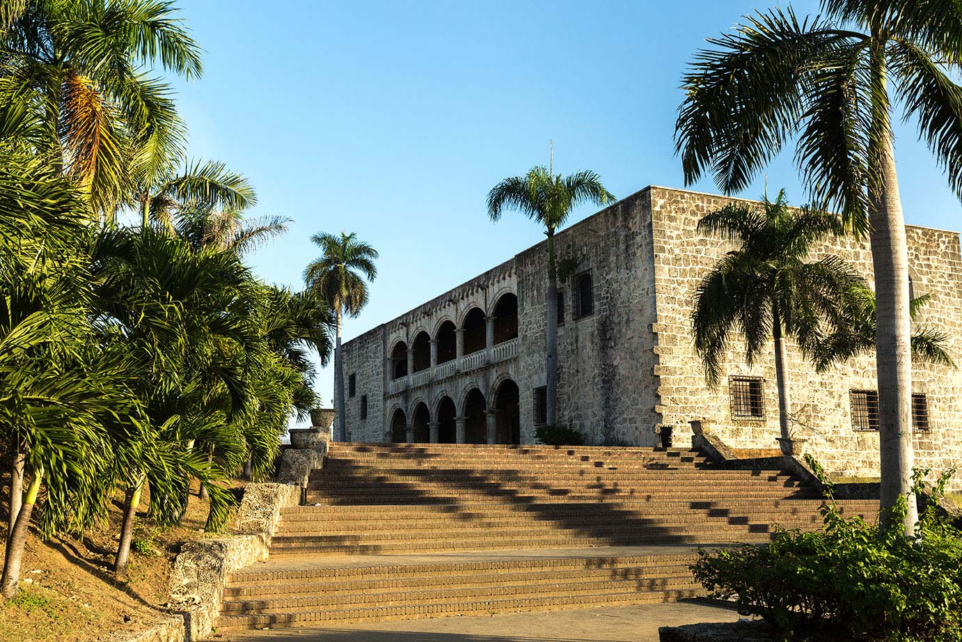 A stone building surrounded by palm trees in Santo Domingo