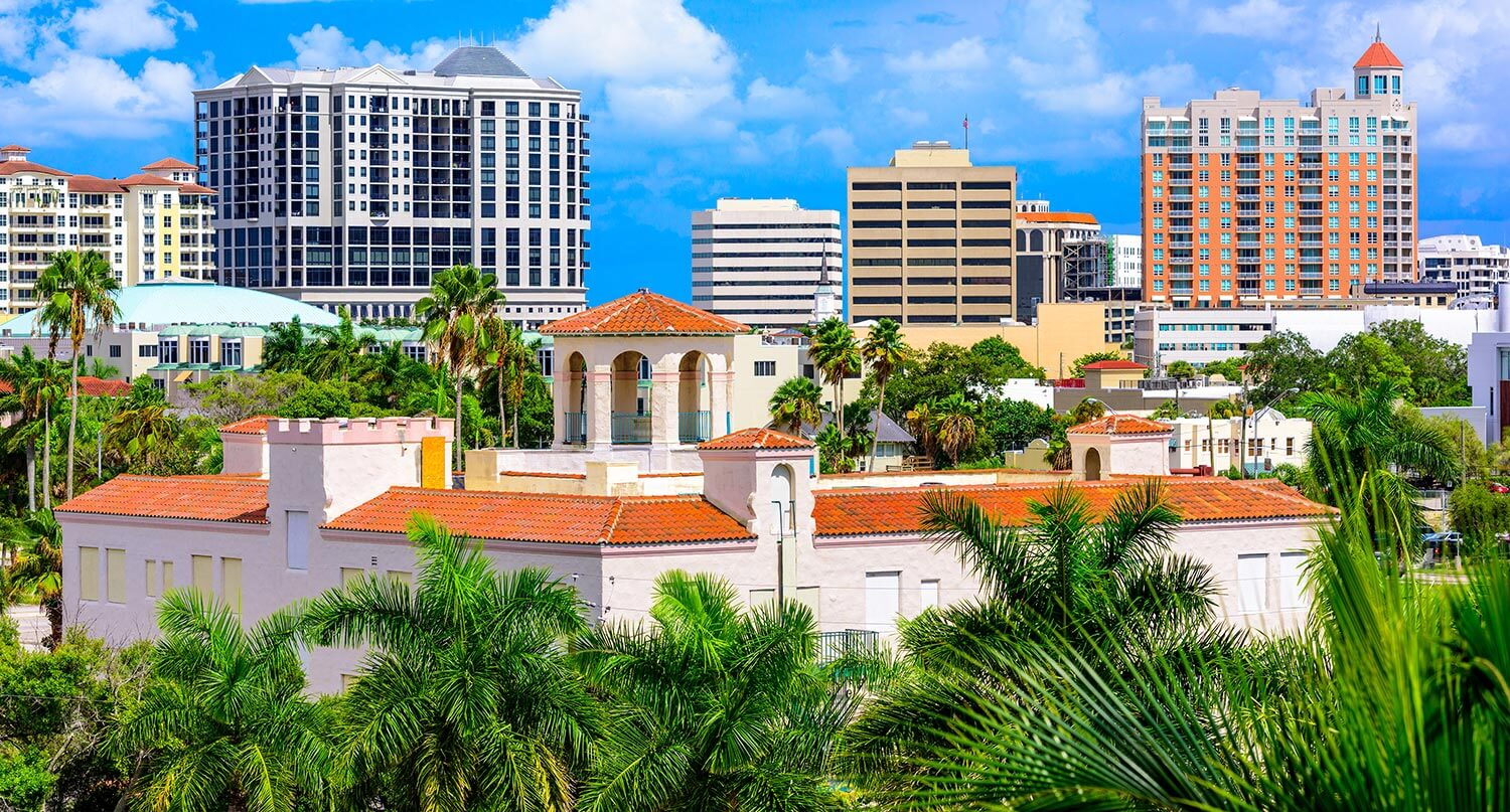 Aerial view of multi-level buildings surrounded by palm trees in Sarasota