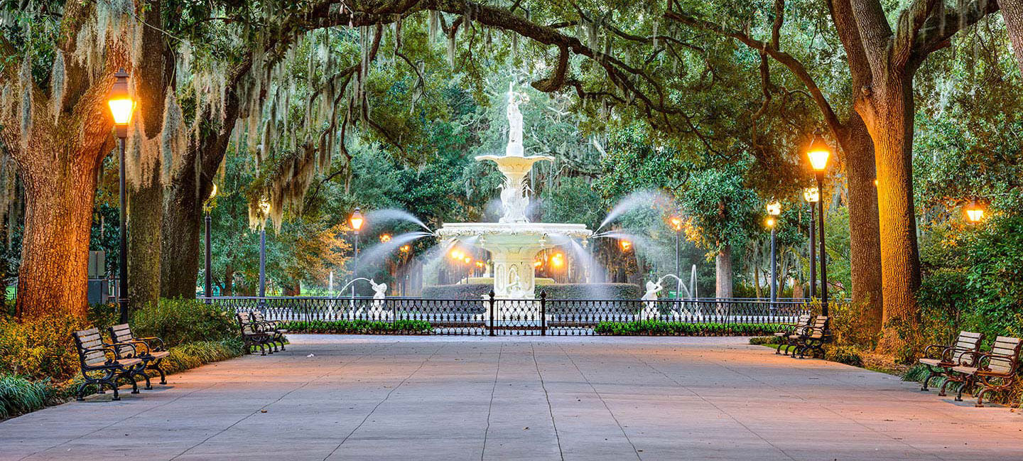A wide tree-lined pathway leads to a large white fountain in Savannah