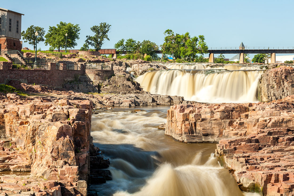 Muddy water rushes between boulders in Sioux Falls