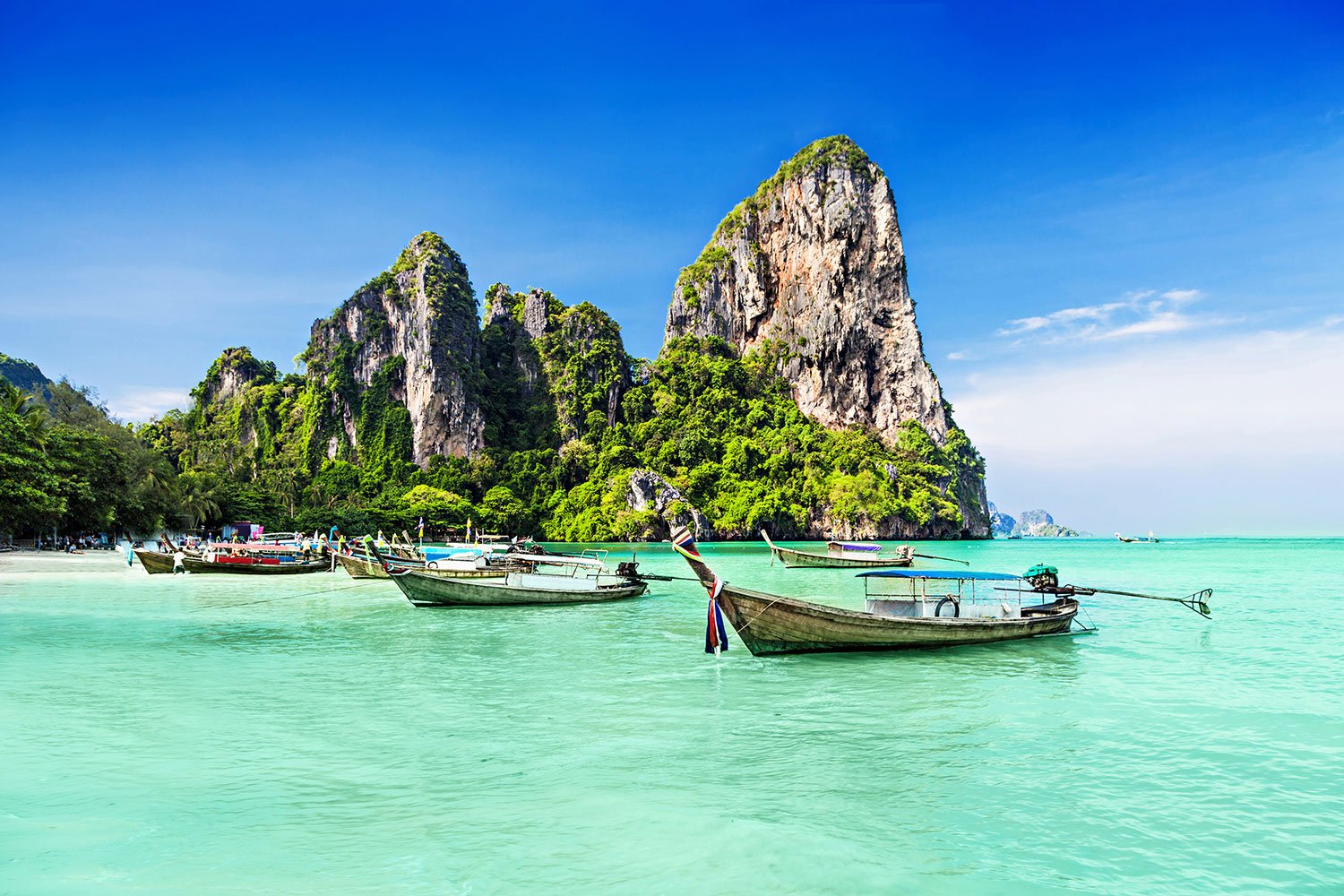 Small boats float in blue-green water next to large rock formations in Thailand