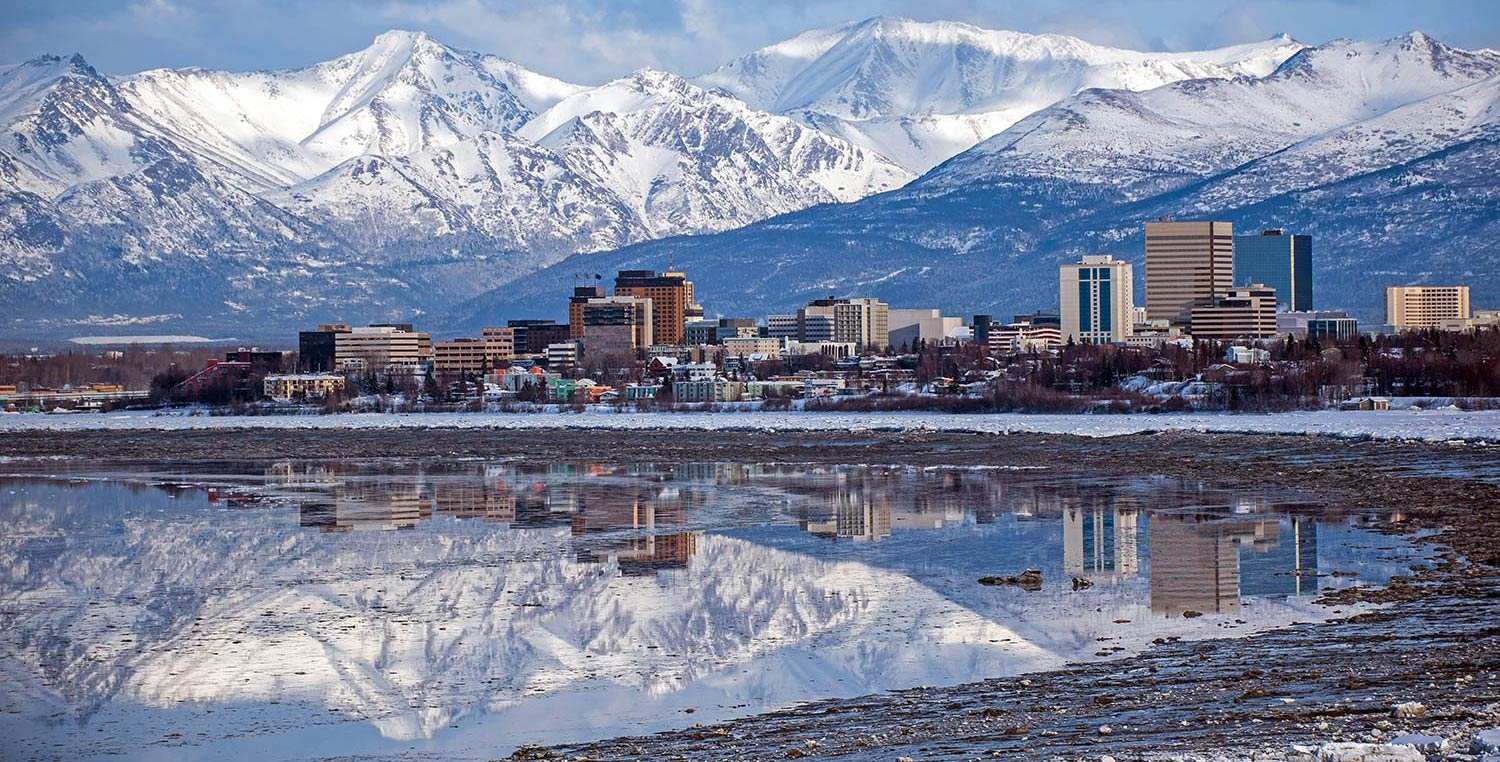 Anchorage skyline and snowy mountains reflect off an inlet