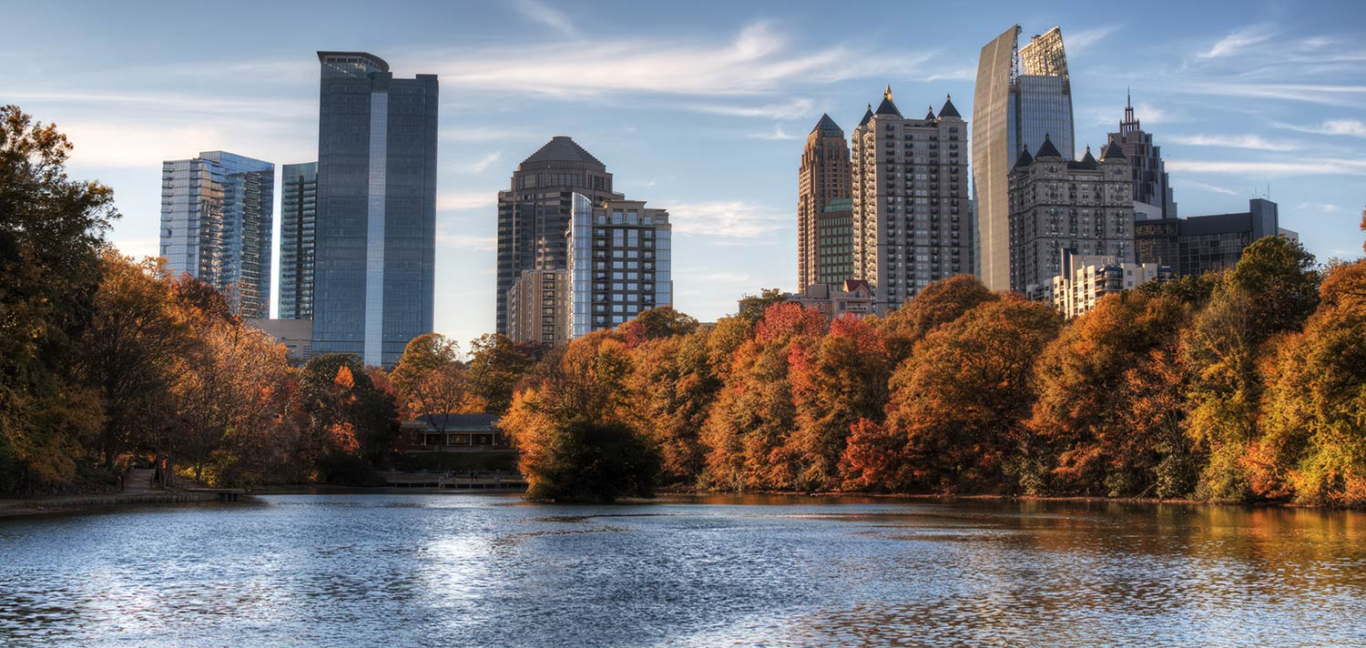Atlanta skyline in autumn complemented by a tree-lined pond
