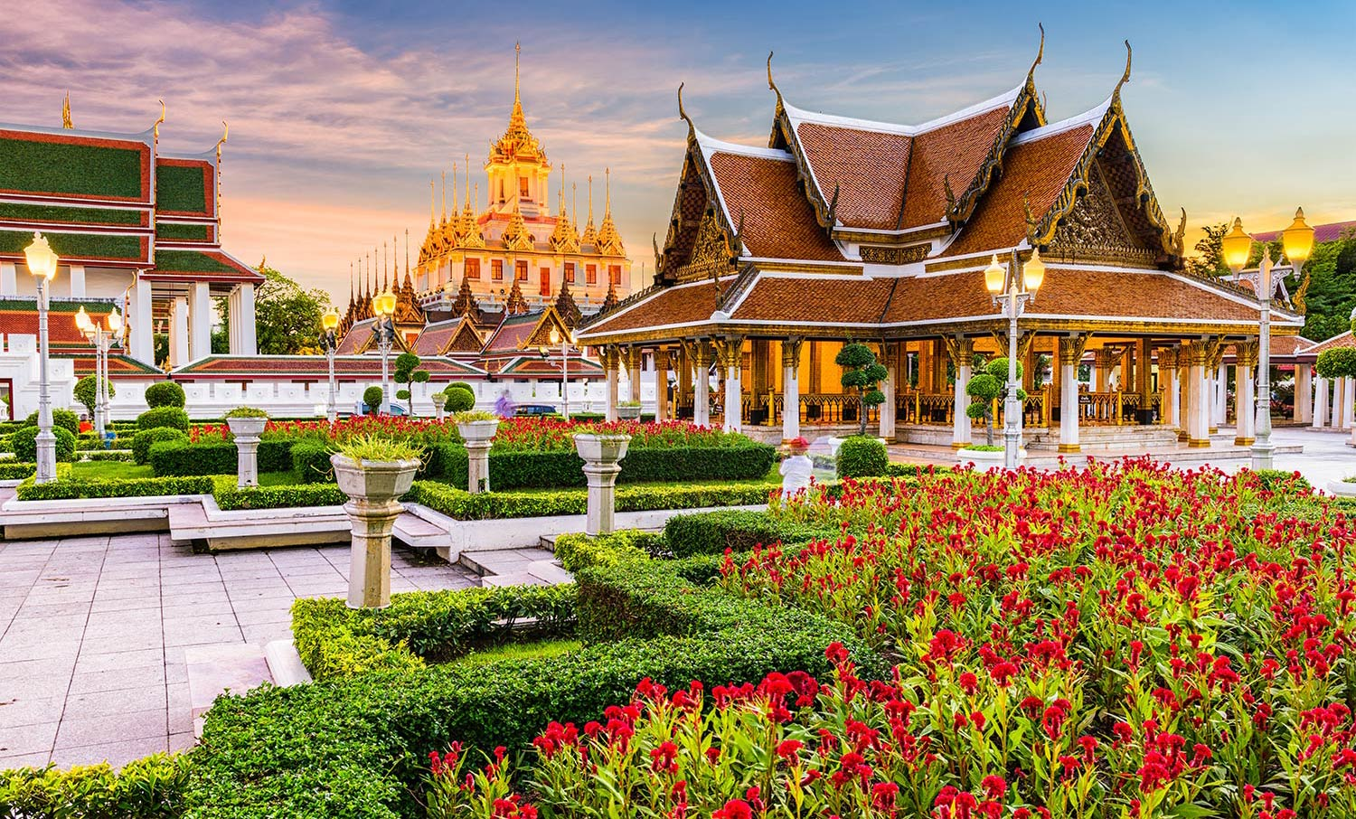 Buddhist temple surrounded by red flowers in Bangkok