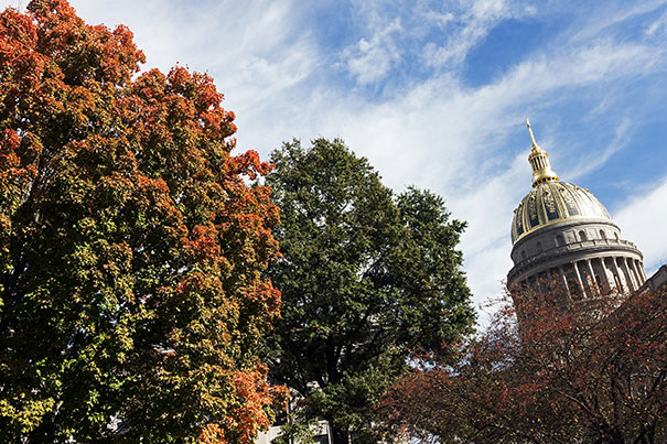 Trees surround the Charleston, WV, State Capitol building in autumn