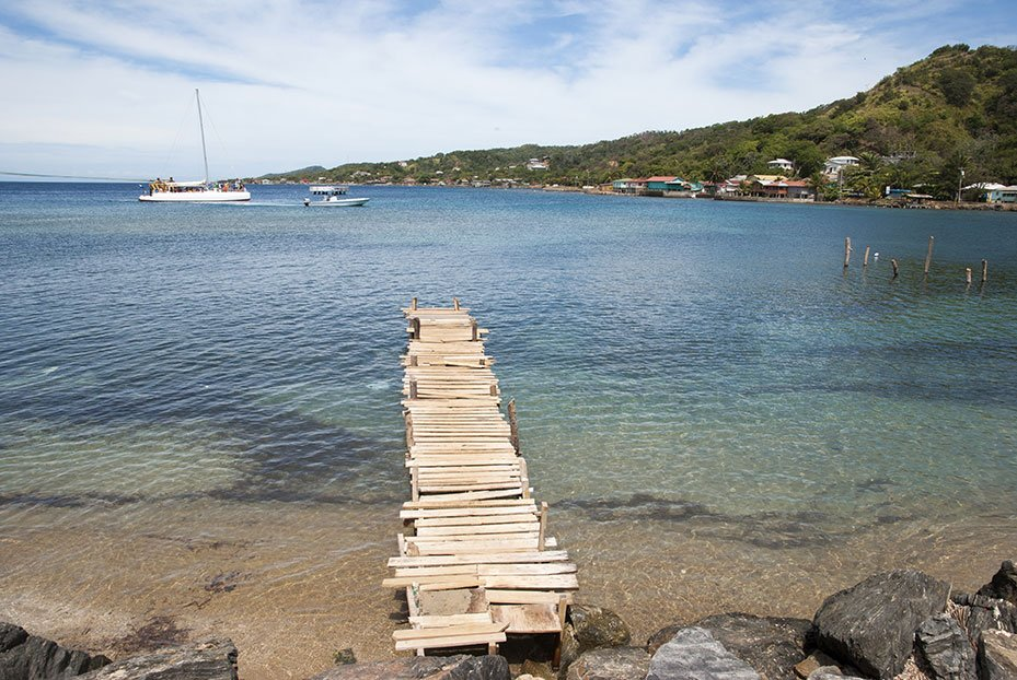 Narrow wooden pier leading into the sea in Coxen Hole
