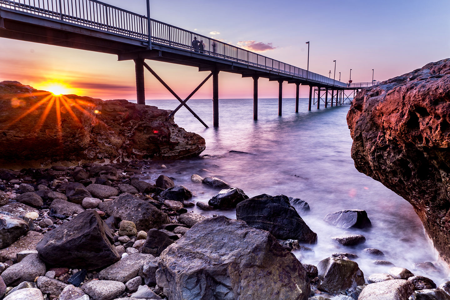 Pier over rushing water in Darwin at sunset
