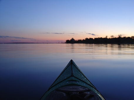 Kayak on Devils Lake at dusk with trees dotting the horizon