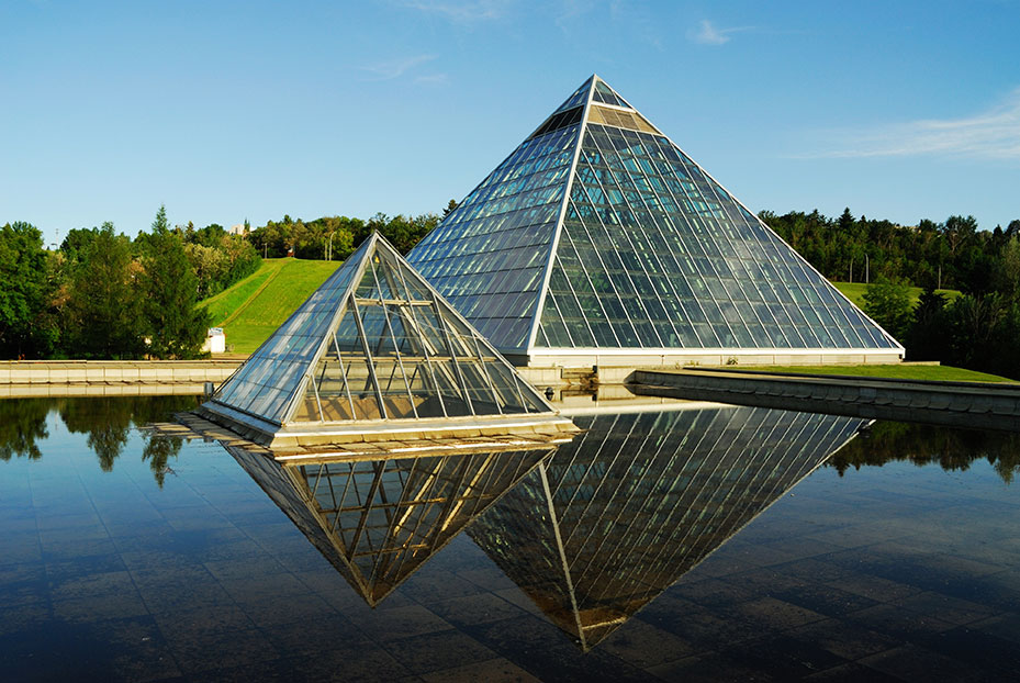 Small and large glass pyramids next to a pool of water in Edmonton
