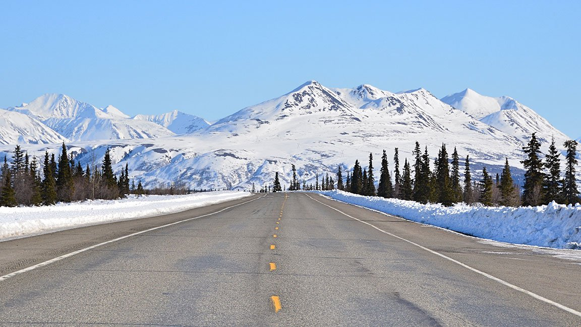 Paved highway in Fairbanks leading toward snowy mountains