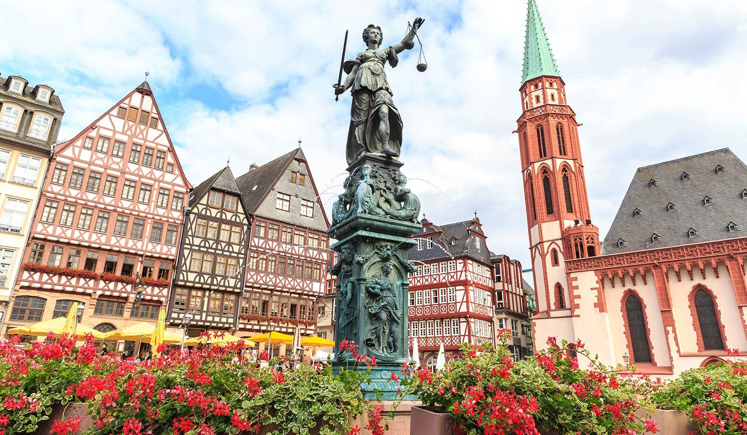 Multilevel buildings, red flowers and a statue in Frankfurt