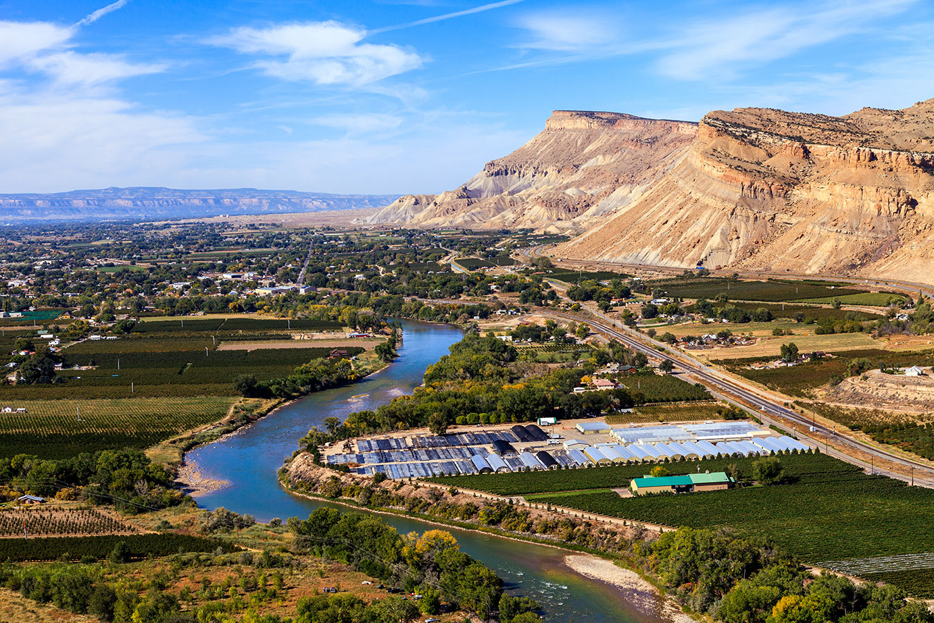 A winding river cuts through a valley near the mountains in Grand Junction