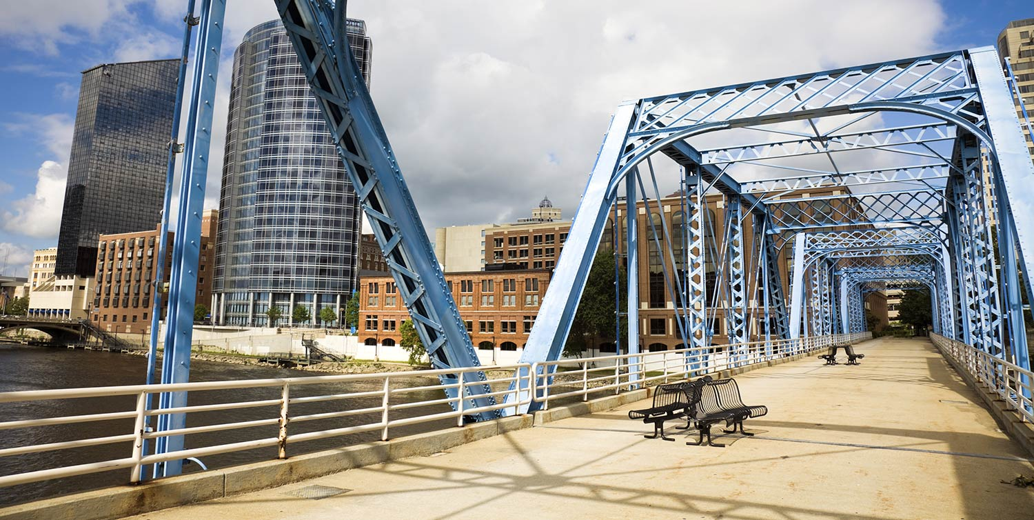 Blue metal bridge leading into the city of Grand Rapids