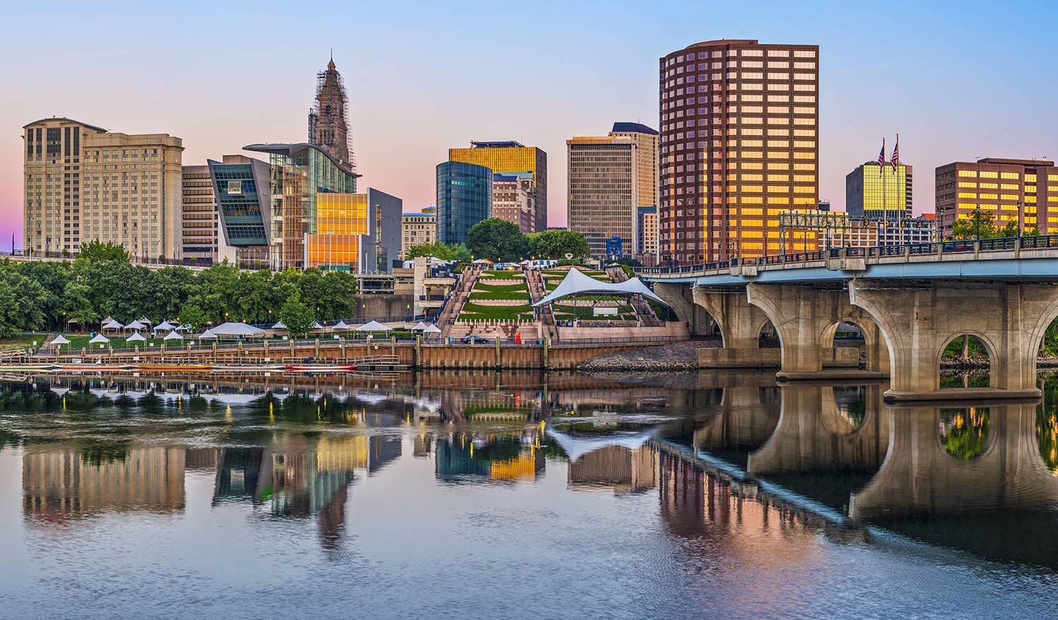 A concrete bridge over a river leads into downtown Hartford